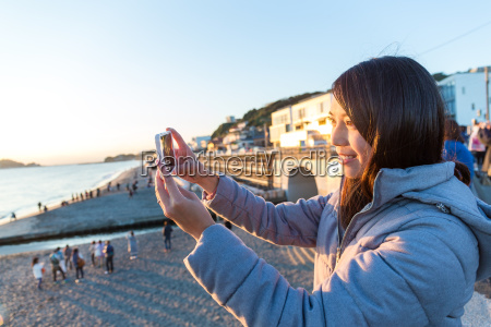 woman taking photo with cellphone under