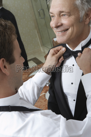 man adjusting senior mans bow tie