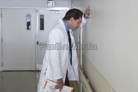 deprimierter doktor der gegen die wand
