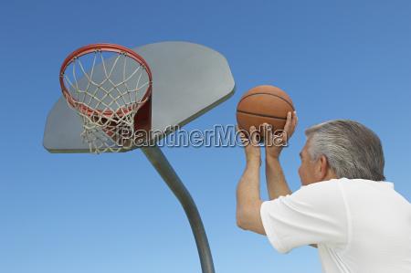 man aiming basketball at hoop