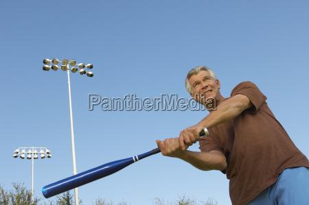 man swinging baseball bat outdoors