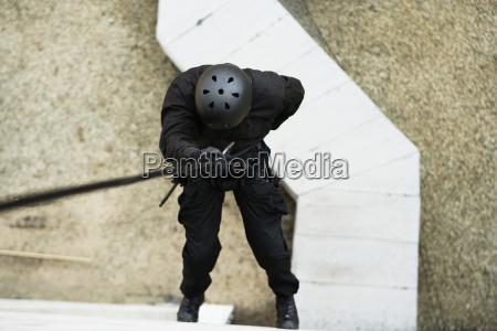 swat team officer rappelling vom bauen