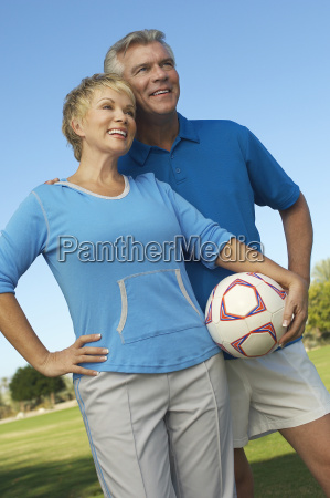couple holding soccer ball looking away
