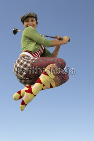 young woman jumping with golf club