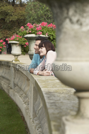 couple looking over wall by potted