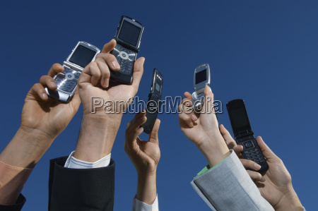 business peoples hands holding mobile phones