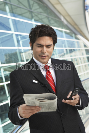businessman reading newspaper while using cellphone