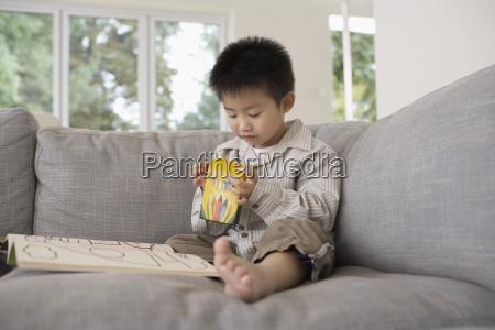 junge mit malbuch sitzen auf sofa