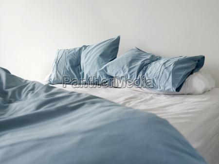 ungemachtes bett mit zerknitterten blauen bettwaesche