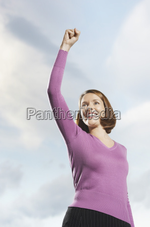 smiling woman with arm raised against