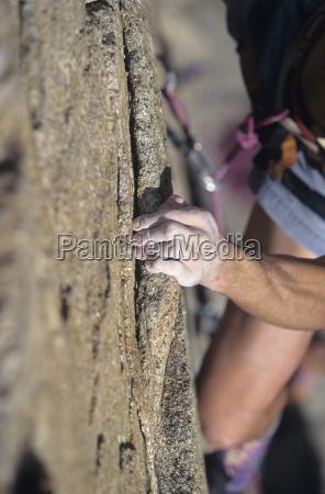 rock climber holding auf cliff