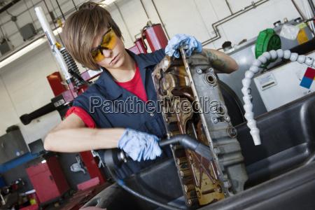 junge weibliche mechaniker arbeiten mit schweissbrenner