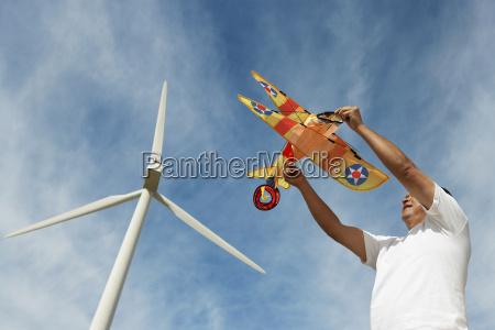man holding airplane kite at wind