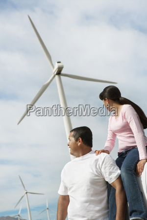 father and daughter near wind turbines
