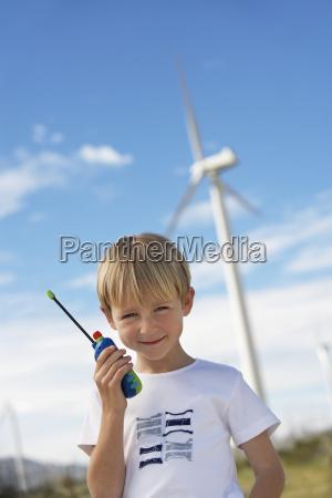 boy holding toy walkie talkie at