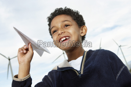 boy playing with paper plane at