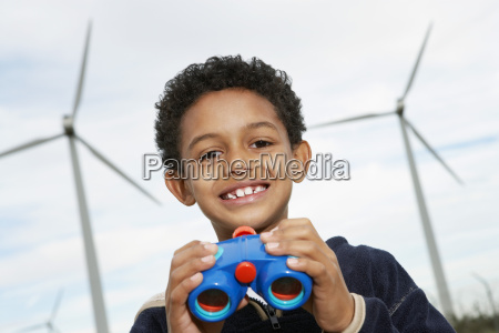 boy holding binoculars at wind farm