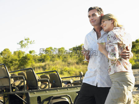 loving couple with wineglasses by jeep