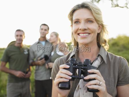 happy woman holding fernglaeser mit freunden
