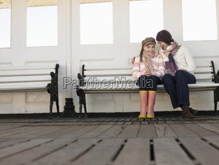mutter und tochter sitzen auf pier