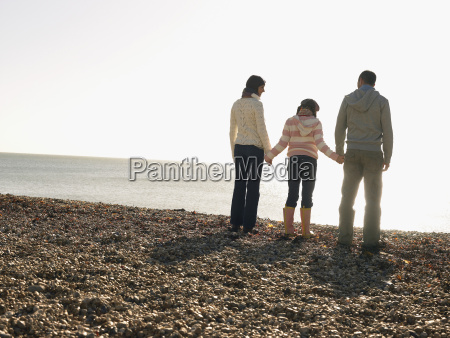 family of three standing on beach