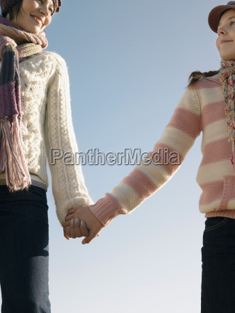 mother and daughter holding hands against