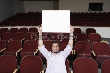 maennlich student raising sign board waehrend