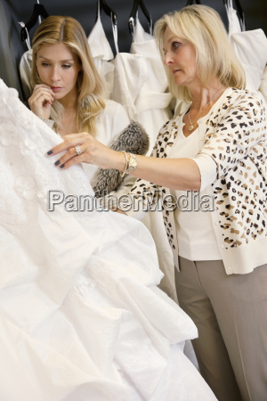 mother selecting wedding dress for young