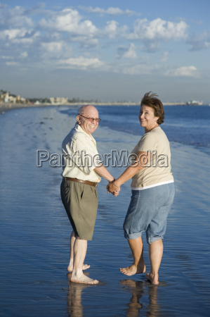 senior couple holding hands at beach