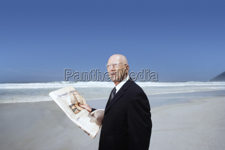 businessman holding newspaper on beach