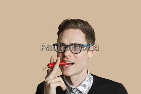 mid adult man smoking red chili