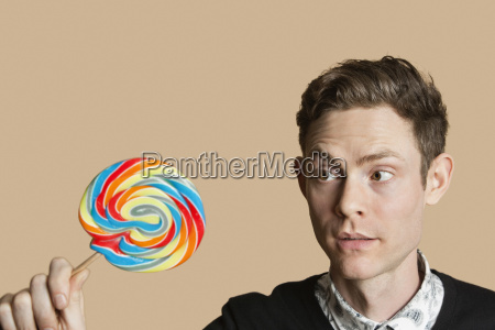 mid adult man looking at lollipop