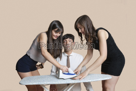young women ironing shocked mans tie