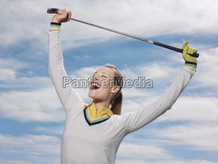 female golfer holding club against sky