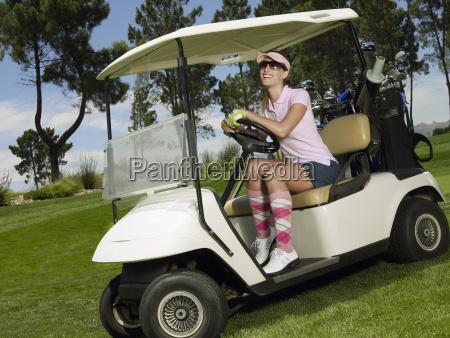 froehliche frau treibt golf cart