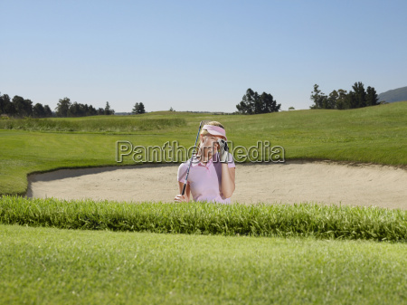 disappointed golfer in sand trap