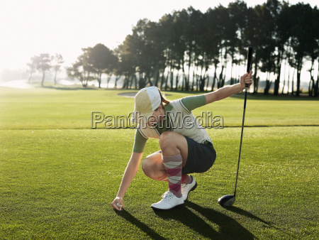 female golfer placing ball on tee