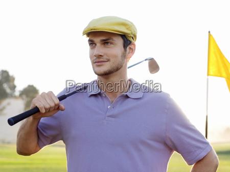 male golfer holding club on golf