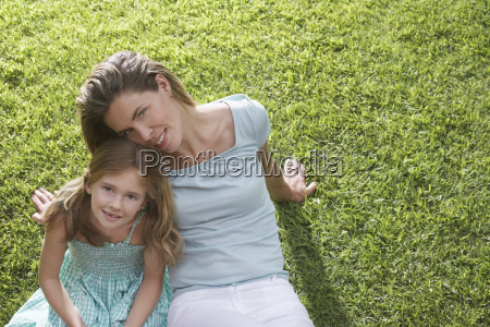 mother with daughter sitting on grass