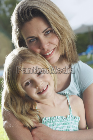 closeup of mother hugging daughter outdoors