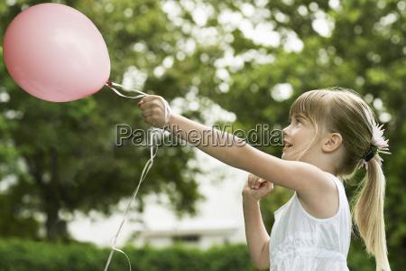 maedchen spielen mit ballon im garten