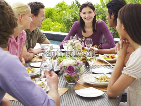 woman with friends enjoying meal outdoors