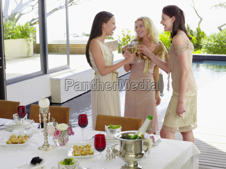 female friends toasting champagne flutes at