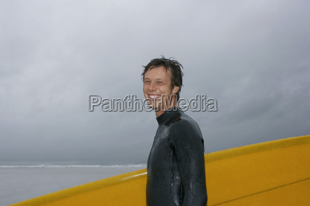 cheerful man with surfboard against cloudy