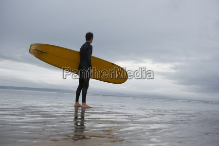 male surfer with surfboard looking at