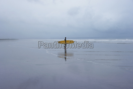 surfer with surfboard walking towards sea
