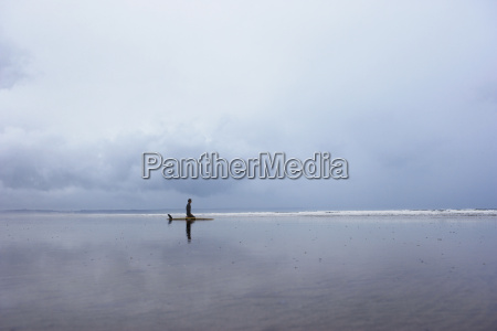 man with surfboard sitting on beach