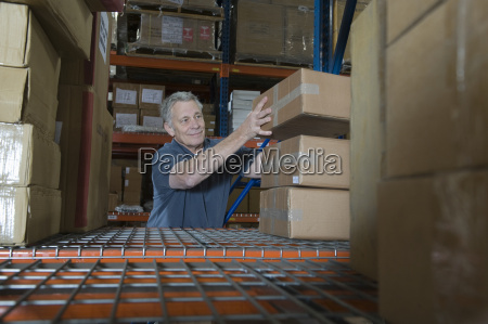 mann stacking boxes in warehouse