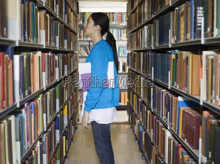 student der buecherregal in der bibliothek