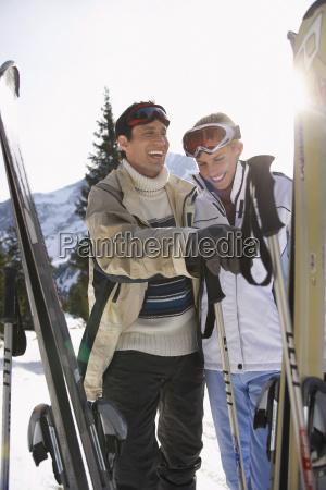 froehliches skifahren paar in warme kleidung